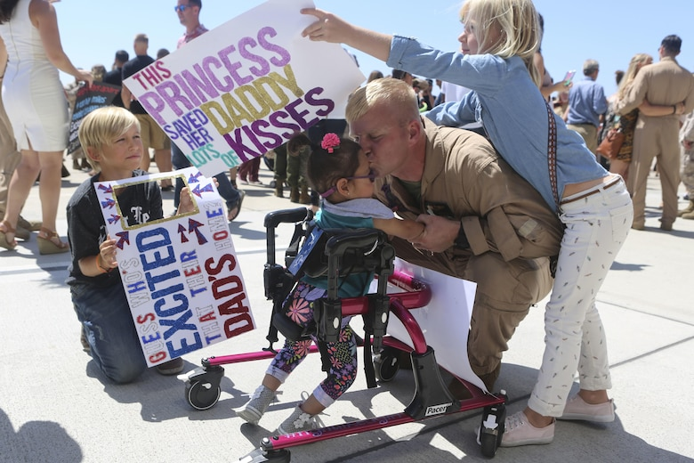 Gunnery. Sgt. Travis Borkowski, crew chief with Marine Medium Tiltrotor Squadron (VMM) 166, reunites with his family after returning from a deployment with the 13th Marine Expeditionary Unit aboard Marine Corps Air Station Miramar, Calif., Sept. 10. During his deployment, Borkowski and his wife Megan officially adopted Briella after fostering her for almost two years. (U.S. Marine Corps photo by Lance Cpl. Harley Robinson/Released)