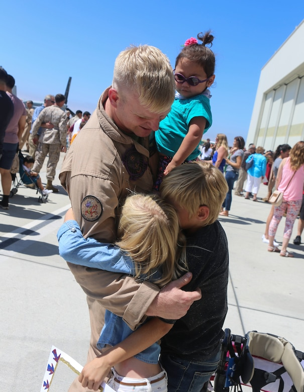 Gunnery Sgt. Travis Borkowski, a crew chief with Marine Medium Tiltrotor Squadron (VMM) 166, reunites with his family during a homecoming ceremony for the aviation combat element of the 13th Marine Expeditionary Unit aboard Marine Corps Air Station Miramar, Calif., Sept. 10. During his deployment, Borkowski and his wife Megan officially adopted Briella Borkowski after fostering her for almost two years. (U.S. Marine Corps photo by Lance Cpl. Harley Robinson/Released)