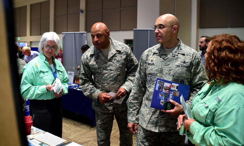Col. David Miller Jr.(right), 460th Space Wing commander and Chief Master Sgt. Rod Lindsey, 460th Space Wing command chief, visit with organizations to learn more about their mission during the Combined Federal Campaign fair Oct. 12, 2016, on Buckley Air Force Base, Colo. More than 70 organizations attended the fair to educate base members on their options for donating. (Air Force photo by Airman Holden S. Faul/Released)