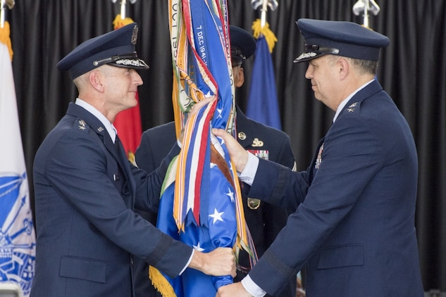Gen. Terrence J. O'Shaughnessy, Pacific Air Force commander, passes the 5th Air Force guidon to the new USFJ and 5th AF commander, Lt. Gen. Jerry P. Martinez, during the USFJ and 5th AF assumption of command ceremony at Yokota Air Base, Japan, Oct. 6, 2016. Martinez was the former director of operations, Headquarters Air Mobility Command, Scott Air Force Base. (U.S. Air Force photo by Yasuo Osakabe/Released)