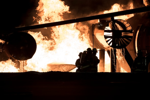 U.S service members battle flames during a simulated aircraft crash burn at Misawa Air Base, Japan, Oct. 12, 2016. The burn, performed by four distinguished visitors, allowed members to experience the processess and challenges that come with fighting an aircraft fire. The DVs were both U.S. Air Force and Navy personnel. As a part of Misawa's Fire Prevention Week, families and other miltary members came and spectated. (U.S. Air Force photo by Airman 1st Class Sadie Colbert)