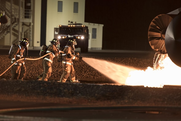 U.S. service members battle flames during a simulated aircraft crash burn at Misawa Air Base, Japan, Oct. 12, 2016. Children were able to meet with firefighters after the event as a part of Misawa's Fire Prevention Week. Fire prevention week also included events such as static displays of firetrucks on a separate day open to all of the community. (U.S. Air Force photo by Airman 1st Class Sadie Colbert)
