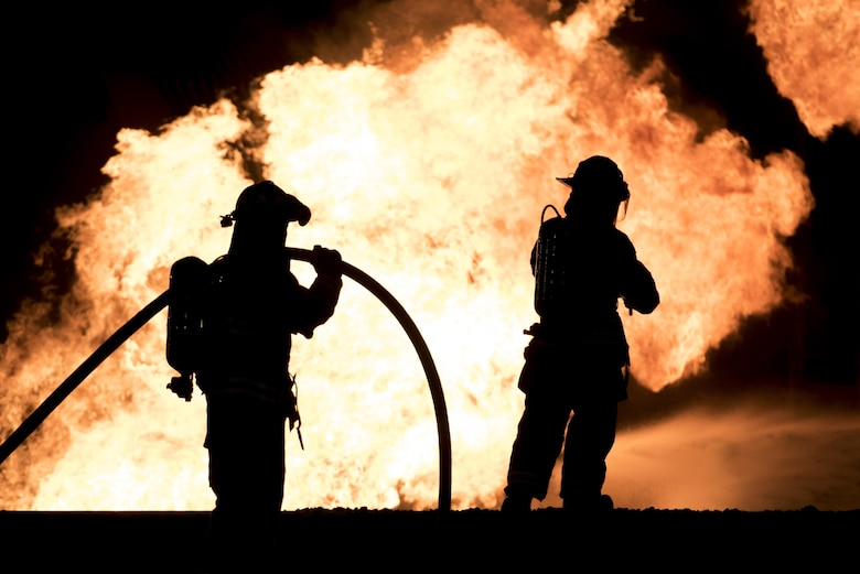 Airmen with the 35th Civil Engineer Squadron fire department steady a hose line to fight a simulated fire at Misawa Air Base, Japan, Oct. 12, 2016. The firehoses connect to firetrucks, which hold up to 3,000 gallons of water per truck. Once water is depleted, firefighters desconnect hoses and hook them up to nearby fire hydrants, enabling firefighters to battle flames. (U.S. Air Force photo by Airman 1st Class Sadie Colbert)