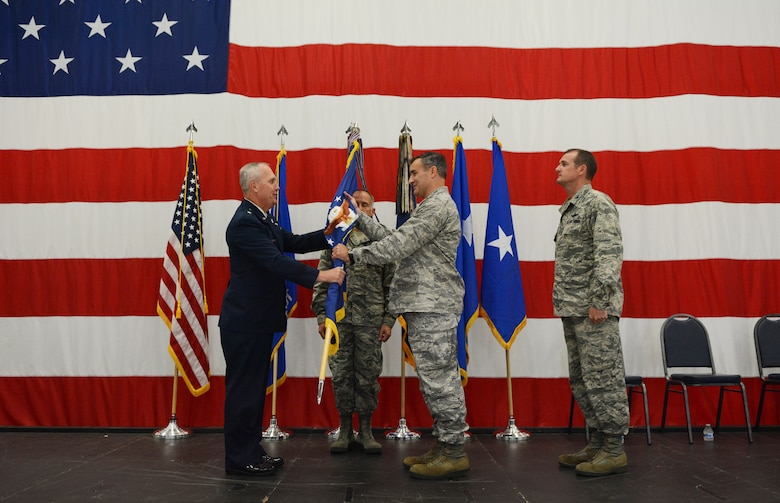 Maj. Gen. Donald P. Dunbar, Wisconsin adjutant general, passed the flag to Col. Erik Peterson, 115th Fighter Wing commander, during a wing change of command ceremony in hangar 406 Oct. 1, 2016. Airmen from the 115 FW attended the event to watch Col. Jeffrey J. Wiegand, former 115 FW commander, relinquish his command to Peterson. (U.S. Air National Guard photo by Staff Sgt. Kyle Russell)