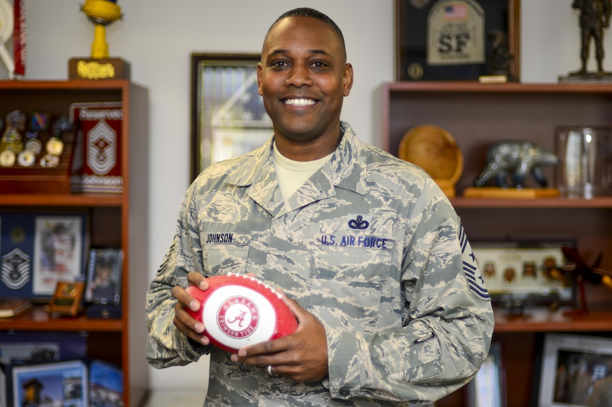 Chief Master Sgt. Anthony Johnson, 7th Air Force command chief, poses with a University of Alabama football in his office at Osan Air Base, Republic of Korea, Oct. 13, 2016. Johnson was recently nominated to be the next Pacific Air Forces command chief master sergeant. (U.S. Air Force photo by Senior Airman Victor J. Caputo)