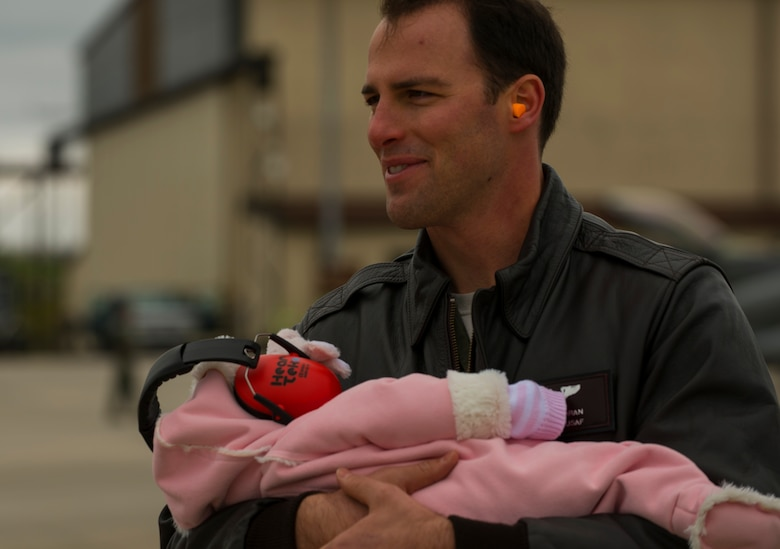 An Airman assigned to the 52nd Fighter Wing cradles an infant while waiting to greet returning Airmen on the flightline at Spangdahlem Air Base, Germany, Oct. 6, 2016. Approximately 300 of the 480th Expeditionary Fighter Squadron's Airmen, who serve in flight, maintenance or support roles for the F-16 Fighting Falcon fighter aircraft, completed a six-month deployment to Southwest Asia by providing close air support and dynamic targeting operations in support of Operation Inherent Resolve. (U.S. Air Force photo by Senior Airman Dawn M. Weber)