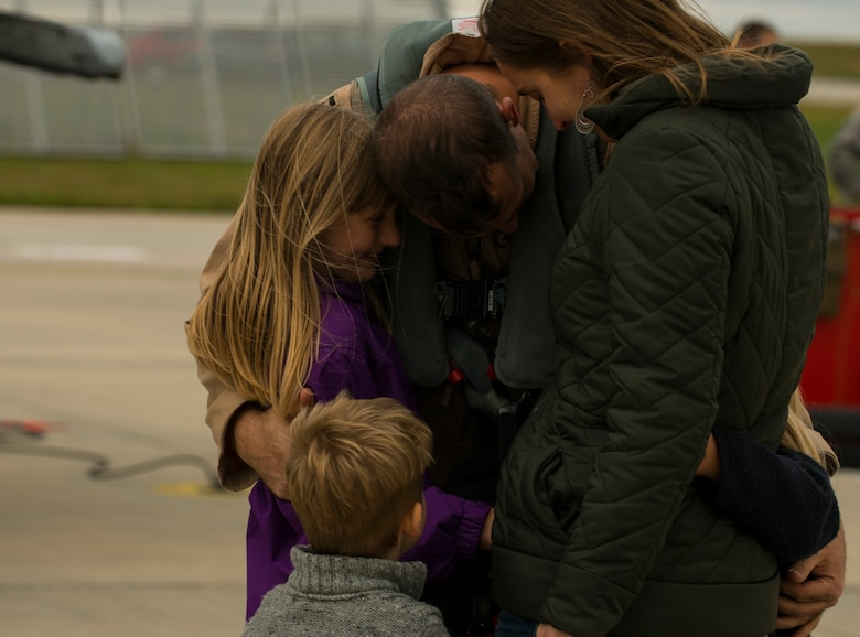 A 480th Expeditionary Fighter Squadron Airman embraces his family on the flightline at Spangdahlem Air Base, Germany, Oct. 6, 2016. Approximately 300 of the squadron's Airmen, who serve in flight, maintenance or support roles for the F-16 Fighting Falcon fighter aircraft, completed a six-month deployment to Southwest Asia by providing close air support and dynamic targeting operations in support of Operation Inherent Resolve. (U.S. Air Force photo by Senior Airman Dawn M. Weber)