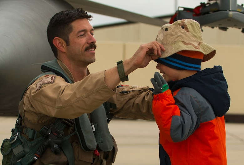 An Airman assigned to the 480th Expeditionary Fighter Squadron places a hat on his son's head on the flightline at Spangdahlem Air Base, Germany, Oct. 6, 2016. Members of the 480th EFS and supporting agencies deployed to support Operation Inherent Resolve. (U.S. Air Force photo by Senior Airman Dawn M. Weber)