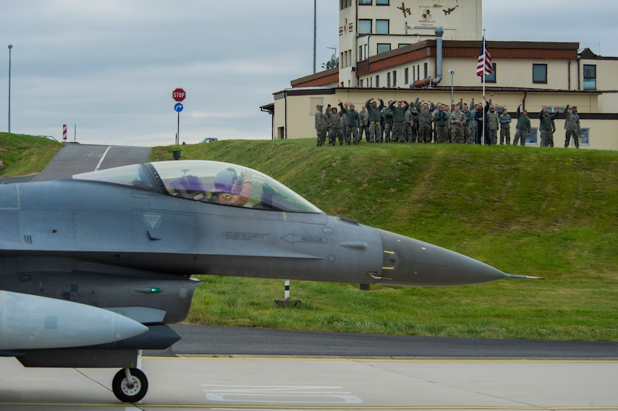 Airmen assigned to the 52nd Fighter Wing wave as an F-16 Fighting Falcon fighter aircraft pilot assigned to the 480th Expeditionary Fighter Squadron during the squadron's return to Spangdahlem Air Base, Germany, Oct. 6, 2016. Approximately 300 of the Airmen, who serve in flight, maintenance or support roles for the F-16, completed a six-month deployment to Southwest Asia by providing close air support and dynamic targeting operations as part of the squadron's first deployment in support of Operation Inherent Resolve. Operation Inherent Resolve aims to eliminate the Da'esh terrorist group and the threat they pose to Iraq, Syria and the wider international community. (U.S. Air Force photo by Staff Sgt. Joe W. McFadden)