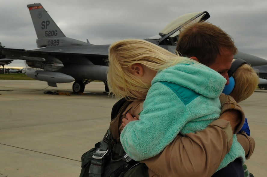 An Airman assigned to the 480th Expeditionary Fighter Squadron reunites with his children during the squadron's return to Spangdahlem Air Base, Germany, Oct. 6, 2016. Approximately 300 of the Airmen, who serve in flight, maintenance or support roles for the F-16 Fighting Falcon fighter aircraft, completed a six-month deployment to Southwest Asia by providing close air support and dynamic targeting operations as part of the squadron's first deployment in support of Operation Inherent Resolve. Operation Inherent Resolve aims to eliminate the Da'esh terrorist group and the threat they pose to Iraq, Syria and the wider international community. (U.S. Air Force photo by Staff Sgt. Joe W. McFadden)