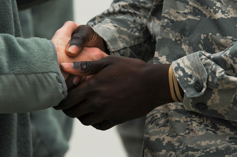 Chief Master Sgt. Edwin Ludwigsen, 52nd Fighter Wing command chief, left, shakes the hand of an Airman assigned to the 480th Expeditionary Fighter Squadron, right, during the squadron's return to Spangdahlem Air Base, Germany, Oct. 12, 2016. Approximately 300 of the Airmen, who serve in flight, maintenance or support roles for the F-16 Fighting Falcon fighter aircraft, completed a six-month deployment to Southwest Asia by providing close air support and dynamic targeting operations as part of the squadron's first deployment in support of Operation Inherent Resolve. Operation Inherent Resolve aims to eliminate the Da'esh terrorist group and the threat they pose to Iraq, Syria and the wider international community. (U.S. Air Force photo by Staff Sgt. Joe W. McFadden)