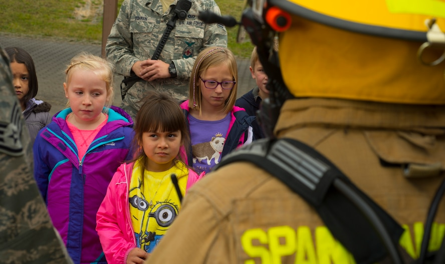 Spangdahelm Elementary School students listen as 52nd Civil Engineer Squadron firefighters teach them about firefighter equipment while visiting SES on Spangdahlem Air Base, Germany,  Oct. 12, 2016. The additional gear a firefighter wears weighs approximately 75 pounds. The firefighters demonstrated the importance of fire safety to the students in observance of Fire Prevention Week. (U.S. Air Force photo by Senior Airman Dawn M. Weber)