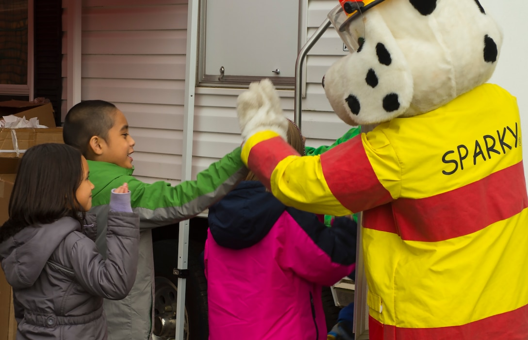 Sparky, 52nd Civil Engineer Squadron firefighters' mascot, high-fives students during a visit at Spangdahlem Elementary School on Spangdahlem Air Base, Germany, Oct. 12, 2016. The firefighters demonstrated the importance of fire safety to students in observance of Fire Prevention Week. (U.S. Air Force photo by Senior Airman Dawn M. Weber)