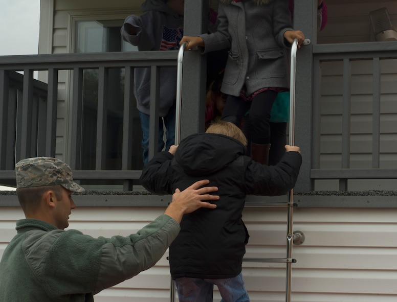 An Airman assigned to the 52nd Civil Engineer Squadron fire department, assists Spangdahlem Elementary School students down a ladder while they practice exiting a building during a fire drill at SES on Spangdahlem Air Base, Germany, Oct. 12, 2016. The pretend house fire taught students what to do if they suspect the house they are in is on fire. (U.S. Air Force photo by Senior Airman Dawn M. Weber)