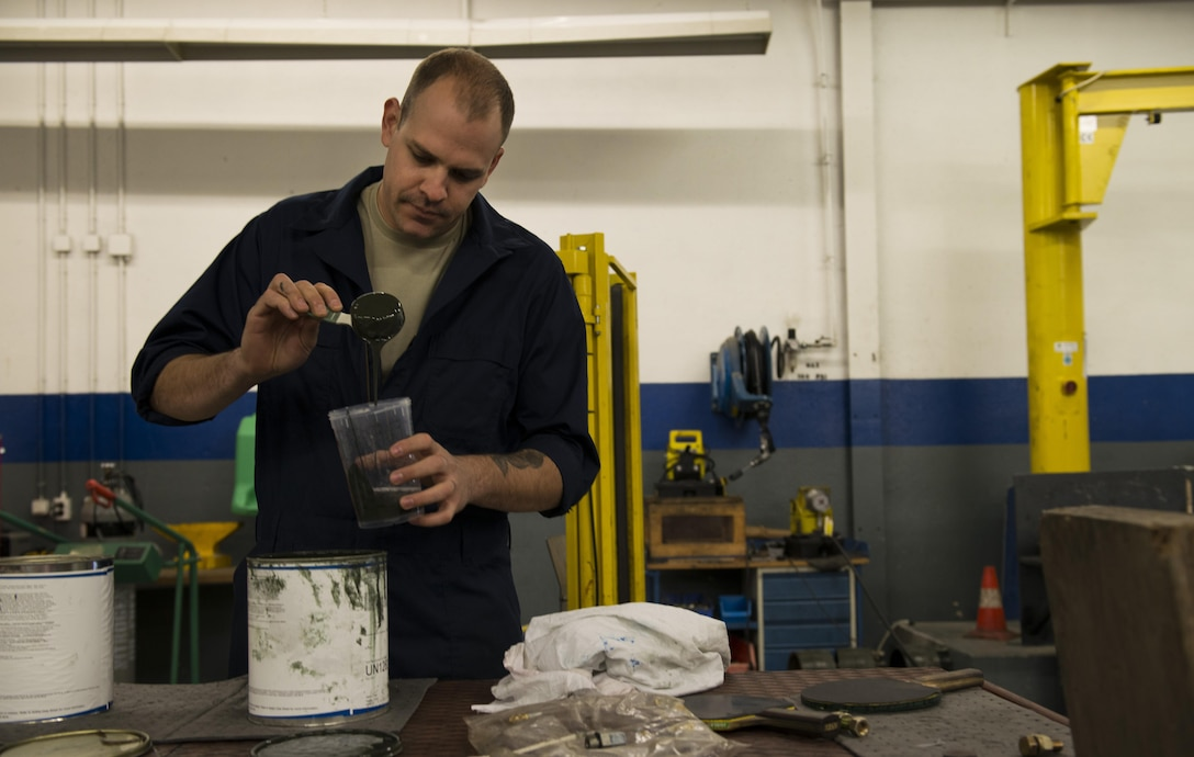 Staff Sgt. Kyle Morris, 435th Construction and Training Squadron aircraft arresting systems depot technician, mixes paint at Ramstein Air Base, Germany, Oct. 13, 2016. Morris mixed the paint to spray over dents and chips on a BAK-12 aircraft arresting system during an overhaul. The 435th CTS is the only squadron within U.S. Air Forces in Europe with the capability to overhaul the systems. (U.S. Air Force photo by Senior Airman Tryphena Mayhugh)
