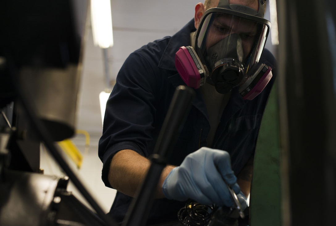Staff Sgt. Kyle Morris, 435th Construction and Training Squadron aircraft arresting systems depot technician, sprays paint on a BAK-12 aircraft arresting system at Ramstein Air Base, Germany, Oct. 12, 2016. The systems decelerate aircraft during landing and require an overhaul every ten years. The 435th CTS overhauls all aircraft arresting systems within U.S Air Forces in Europe. (U.S. Air Force photo by Senior Airman Tryphena Mayhugh)