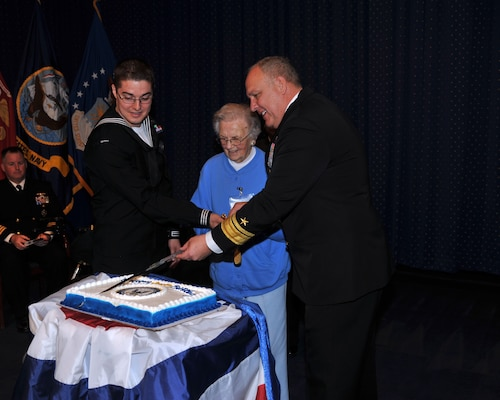 Youngest attendee Navy Petty Officer 2nd Class Adrian Walter (left), oldest attendee Barbara Danaher and host Rear Adm. Scott Jerabek cut a cake for the Navy's birthday ceremony at the McNamara Headquarters Complex, Fort Belvoir, Virginia, Oct. 12.
