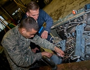 (From left) Senior Airman Cody Crawford, 5th Maintenance Squadron aerospace ground equipment journeyman, and Airman 1st Class Jeremy Graff, 5 MXS AGE apprentice, work on a malfunctioning engine at Minot Air Force Base, N.D., Oct. 5, 2016. The AGE Airmen are responsible for upholding equipment standards by performing routine maintenance and inspections. (U.S. Air Force photo/Airman 1st Class Jonathan McElderry)