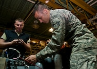 (From left) Senior Airman James Kopp and Senior Airman Cody Crawford, 5th Maintenance Squadron aerospace ground equipment journeymen, check an exhaust cap on a generator at Minot Air Force Base, N.D., Oct. 5, 2016. The AGE Airmen perform a wide variety of tasks, from repairing malfunctioning engines to performing inspections on generators. (U.S. Air Force photo/Airman 1st Class Jonathan McElderry)