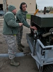 (From left) Staff Sgt. John Dickelman, 5th Maintenance Squadron aerospace ground equipment craftsman and Airman 1st Class Michael Kearns, 5 MXS AGE apprentice, check the voltage on a generator at Minot Air Force Base, N.D., Oct. 5, 2016. The AGE Airmen are responsible for ensuring all generators on base are serviceable. (U.S. Air Force photo/Airman 1st Class Jonathan McElderry)