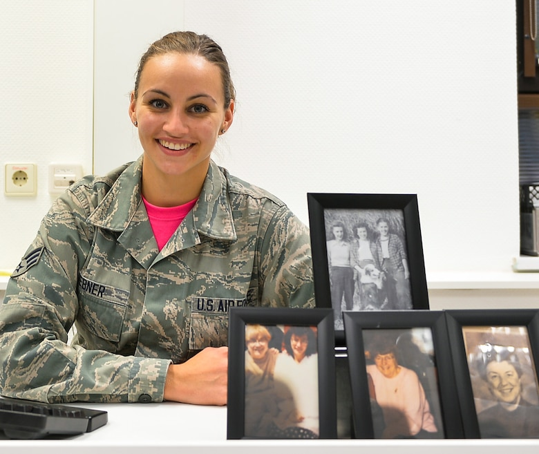 Senior Airman Jordan Hebner, 86th Dental Squadron dental technician, poses with portraits of her grandmother and great-aunts at Ramstein Air Base, Germany. Hebner's grandmother and great-aunts have been affected by breast cancer, which is the second most common cancer for women in the United States. (U.S. Air Force photo by Airman 1st Class Joshua Magbanua)