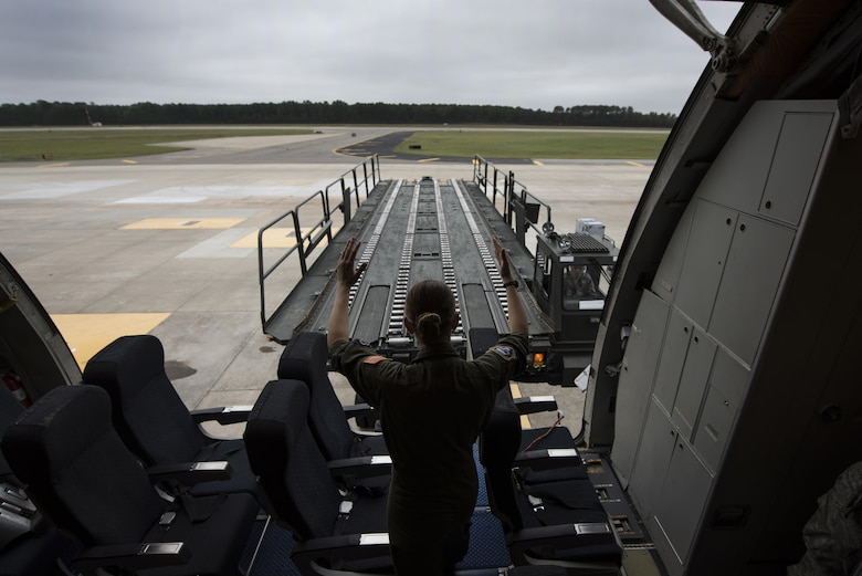 Senior Airman Hannah Byers, a 32nd Air Refueling Squadron crew chief, marshals a K Loader into position Oct. 6, 2016, at Seymour Johnson Air Force Base, N.C. A KC-10A Extender from Joint Base McGuire-Dix-Lakehurst, N.J., helped move essential equipment as more than 40 F-15E Strike Eagles and six KC-135R Stratotankers were repositioned to Barksdale AFB, La., as a precautionary measure to avoid potential damage from high winds associated with Hurricane Matthew. (U.S. Air Force photo/Senior Airman Brittain Crolley)