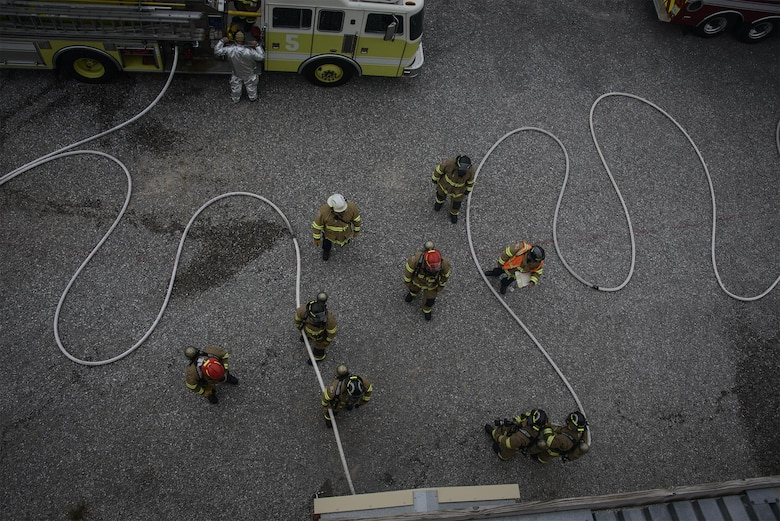 Firefighters safely place charged lines during training at Vance Air Force Base, Okla., Oct. 12, 2016. Vance AFB Fire Department personnel conducted training events and visited shops across the base to talk about fire prevention and safe practices as part of Fire Prevention Week. (U.S. Air Force photo/David Poe)
