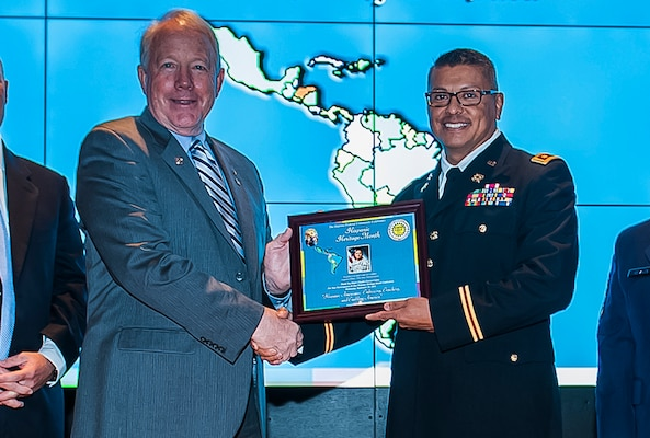 James McClaugherty, DLA Land and Maritime acting commander (left) presents Maj. Claudio Garcia-Castro with a framed program from DLA Land and Maritime's National Hispanic Heritage Month program. Garcia-Castro shared his story of overcoming cultural obstacles and becoming a commissioned officer in the U.S. Army.