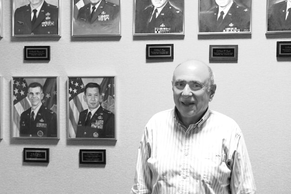 Bruce Telfeyan, a lifelong meteorologist who has spent the last 23 years at the 557th Weather Wing, stands before a wall of past weather commanders in the Wing at Offutt Air Force Base, Neb., Sept. 14, 2015. Throughout his time at the wing, Telfeyan has seen most of these commanders come and go.