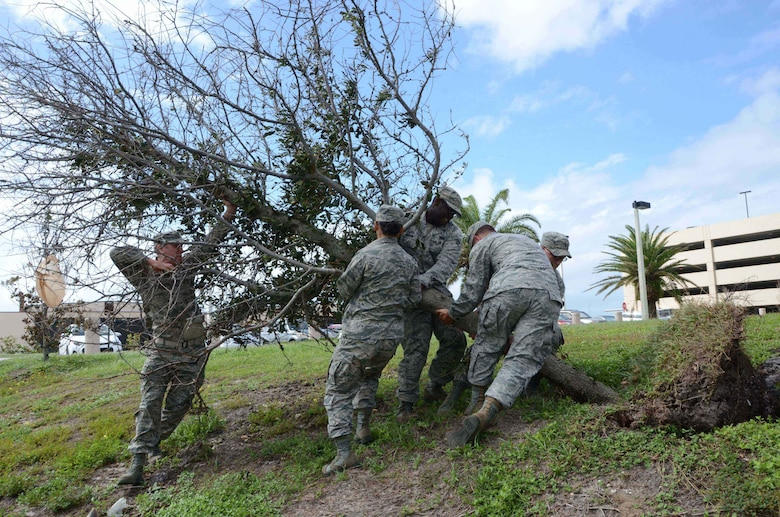 Airmen from the Air Force Technical Applications Center at Patrick AFB, Fla., lift a downed live oak tree after it was uprooted during Hurricane Matthew Oct. 7, 2016.  Picture from left to right:  Maj. Jeremiah Betz, 1st Lt. Pamela Zhang, Senior Airman Donelle Gibson, Capt. Taylor Youtsler and 1st Lt. Michael Duff. (U.S. Air Force photo by Susan A. Romano)