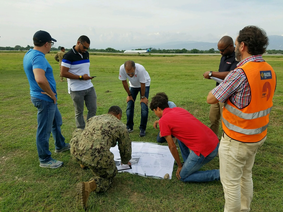 "An engineer from the U.S. Naval Construction Forces ""Seebees"" (center, in fatigues) and personnel from a DLA Troop Support contractor review plans for a helicopter pad at Toussaint L'Ouverture International Airport, Port au Prince, Haiti, October 2016."