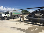 Matt Moshier (left), a DLA Energy customer account specialist, discusses fuel delivery with a pilot from the Army's 1st Battalion, 228th Aviation Regiment, Port-au-Prince, Haiti, October 2016.