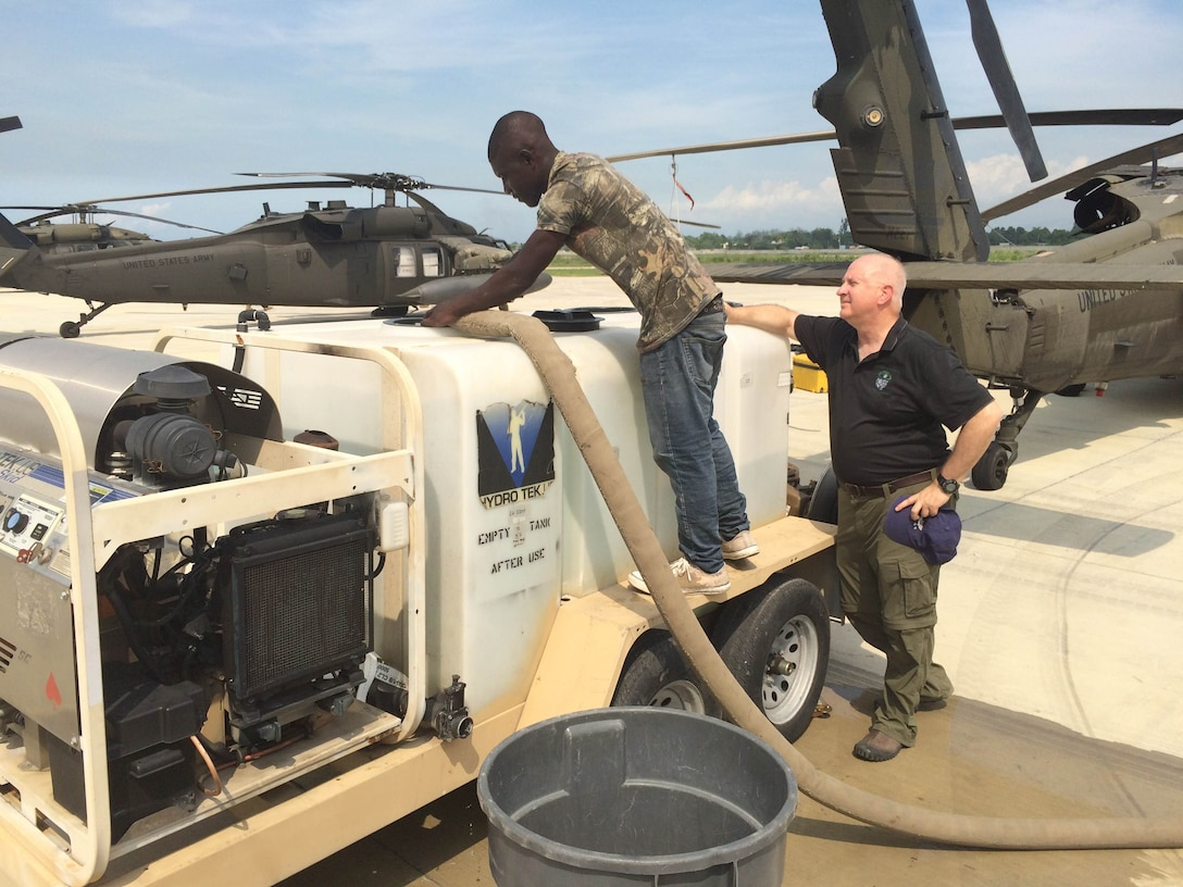 Craig Hill (right), an expeditionary contracting officer for DLA's Joint Contingency Acquisition Support Office, observes a DLA Troop Support contractor fill an aircraft wash tank with non-potable water at Port-au-Prince, Haiti, October 2016. This practice conserved potable water for human consumption.