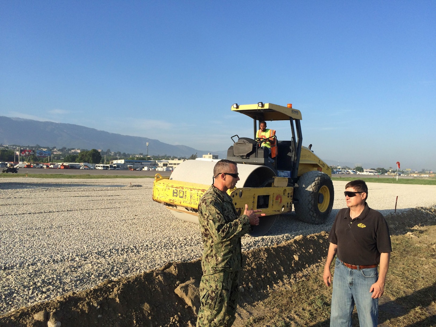 Navy Capt. Paul Haslam (left), commander of the DLA Rapid Deployment Team, discusses a project to build a helicopter pad with Troop Support liaison officer Robert Cunningham, Port-au-Prince, Haiti, October 2016.
