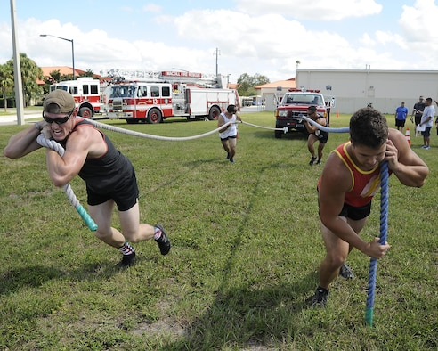 A participating team pulls a vehicle towards the finishing line during the MacDill's Inaugural Firefighter's Challenge at MacDill Air Force Base, Fla., Oct. 14, 2016. During the event, teams of four participated and performed both individual and group tasks in order to complete the challenge. (U.S. Air Force photo by Airman 1st Class Mariette Adams)