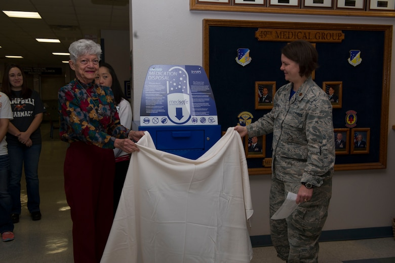 Matilda Smith, a retiree and pharmacy regular, and Maj. Rebekah, the 49th MDG pharmacist, unveil the pharmacy's new medication return container, known as a MedSafe. It will assist in preventing medication abuse, accidental poisonings and environmental contamination from unusable or unwanted medications from patient's homes. (Last names are being withheld due to operational requirements. U.S. Air Force photo by Tech. Sgt. Matthew Rosine.)