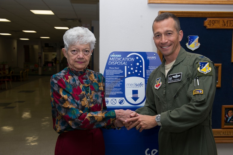 Col. Houston Cantwell, the 49th Wing commander, shakes hands with Matilda Smith, the first person to donate medications as part of the medical group's ceremony, Oct. 14, 2016. (U.S. Air Force photo by Tech. Sgt. Matthew Rosine.)
