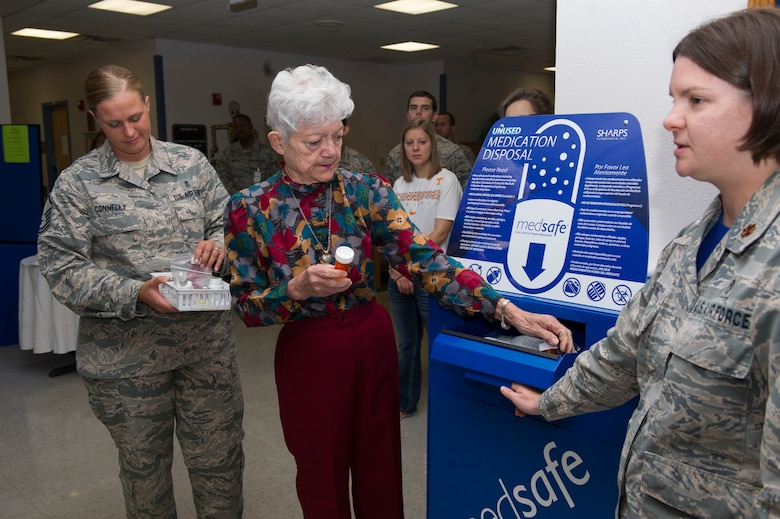 Matilda Smith, a retiree and pharmacy regular, deposits unused medications into the 49th Medical Group pharmacy's new medication return container. Smith was the first person to donate medications as part of the medical group's ceremony, Oct. 14, 2016. (U.S. Air Force photo by Tech. Sgt. Matthew Rosine.)
