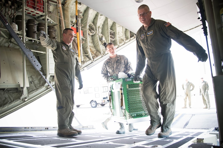 Members of the 36th Aeromedical Evacuation Squadron load equipment onto a 53rd Weather Reconnaissance Squadron WC-130J Super Hercules aircraft during a training mission Oct. 14 out of Keesler Air Force Base, Miss. This mission was the units' first time sharing an aircraft for a training mission. (U.S. Air Force photo/Senior Airman Heather Heiney)