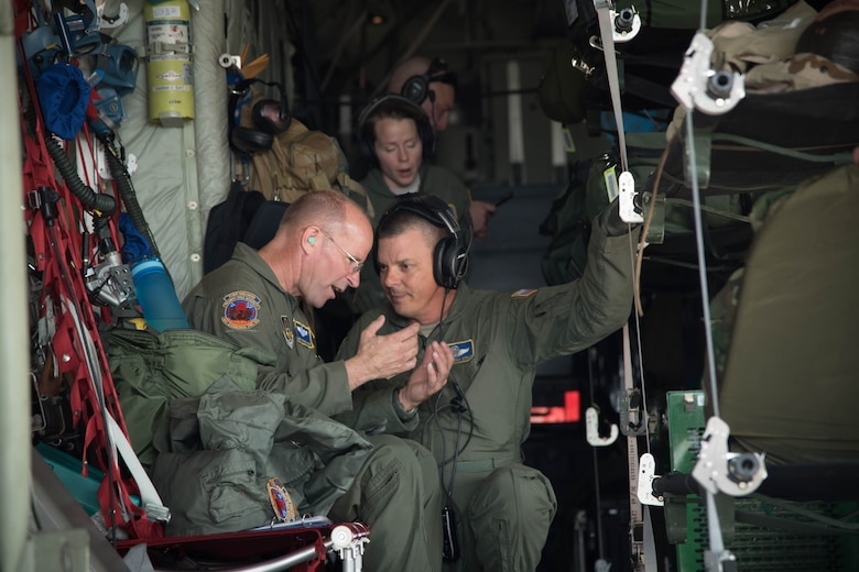 Senior Master Sgt. Michael Bolin and Senior Master Sgt. Tony Stout, 36th Aeromedical Evacuation Squadron aeromedical evacuation technicians, discuss their objectives in the back of a 53rd Weather Reconnaissance Squadron WC-130J Super Hercules aircraft Oct. 14 for a training mission out of Keesler Air Force Base, Miss. This mission was the units' first time sharing an aircraft for a training mission. (U.S. Air Force photo/Senior Airman Heather Heiney)