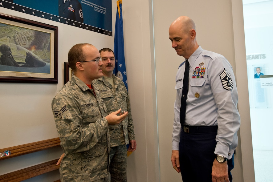 SrA Zachary Thompson, 113th Logistics Readiness Squadron, DC Air National Guard, and Master Sgt. Robert Thorpe, ANG Manpower, Personnel and Services Directorate, present Airman to Airman Coin #12 to the Command Chief Master Sergeant of the ANG, Ronald C. Anderson, October 14, 2016. Thompson and Thorpe created the coin project as a way for enlisted Airmen to recognize each other for their efforts in the moment, and to spur a culture change to focus on positive actions rather than negative ones. (U.S. Air National Guard photo by Staff Sgt. John E. Hillier)