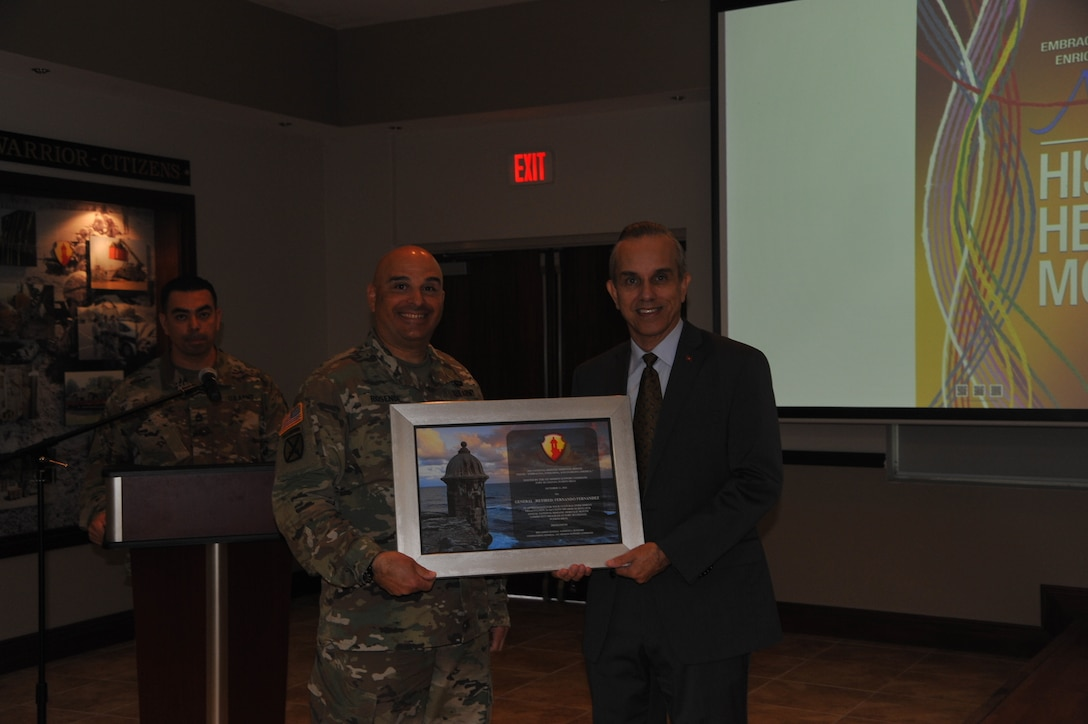 Brig. Gen. Alberto C. Rosende, commanding general for the 1st Mission Support Command, presents Brig. Gen. (Ret.) Fernando Fernandez with a token of appreciation during the Hispanic Heritage event held at Ramos Hall on Fort Buchanan, Puerto Rico, October 15th.