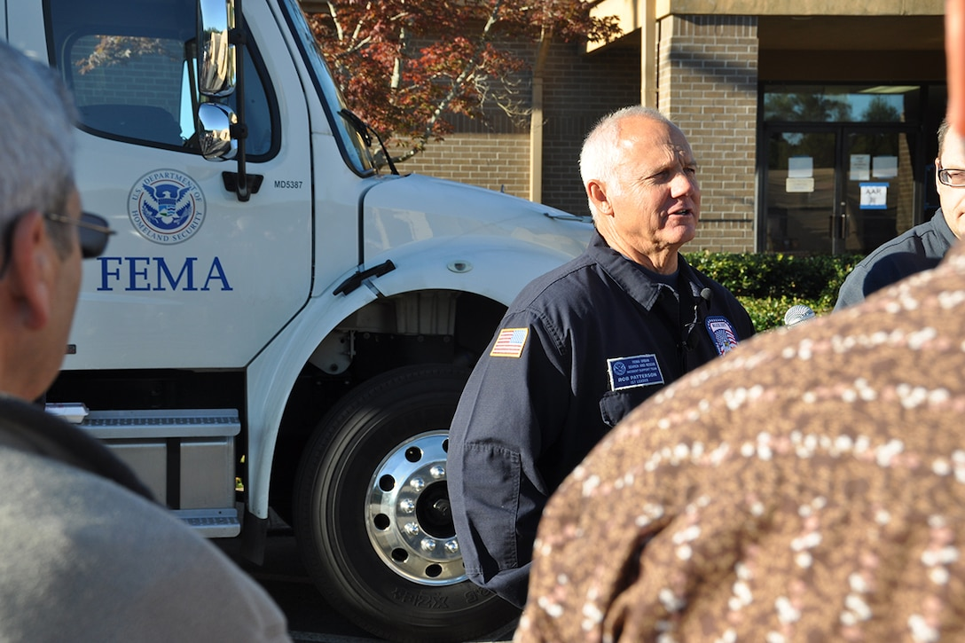 Rob Patterson, FEMA Urban Search and Rescue Blue Incident Support Team leader, speaks to several media outlets at a FEMA command post location on Dobbins Air Reserve Base, Georgia Oct. 12, 2016. Dobbins served as a staging location for the team while they provided rapid federal response to local, federal, state and tribal agencies in support of Hurricane Matthew. (U.S. Air Force photo/James Branch)