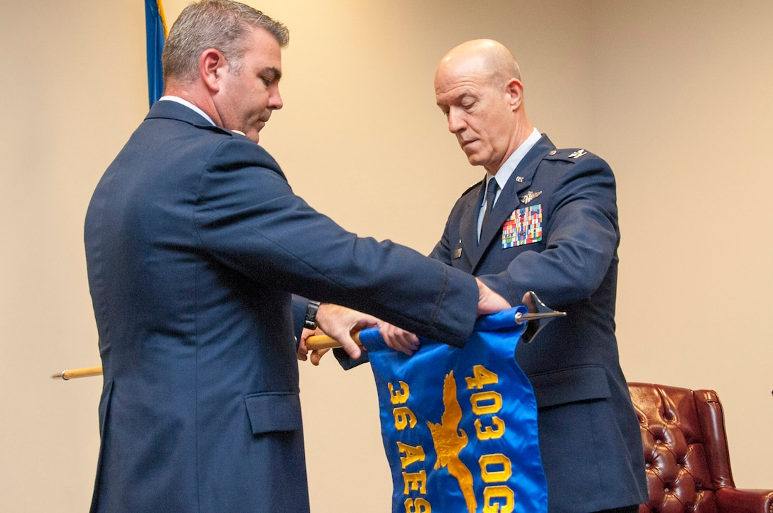 Col. Thomas Hansen (right), 36th Aeromedical Evacuation Squadron commander, and Lt. Col. Brian May, 403rd Operations Group commander, unfurl the 36th AES guidon during the squadron's redesignation ceremony Oct. 15, 2016, at Keesler Air Force Base, Mississippi. The unit relocated to Keesler AFB from Pope Field, N.C., and the squadron members are tasked with transporting wounded Soldiers, Sailors, Airmen and Marines by air to locations where they can receive critical medical care. (U.S. Air Force photo/Tech. Sgt. Ryan Labadens)