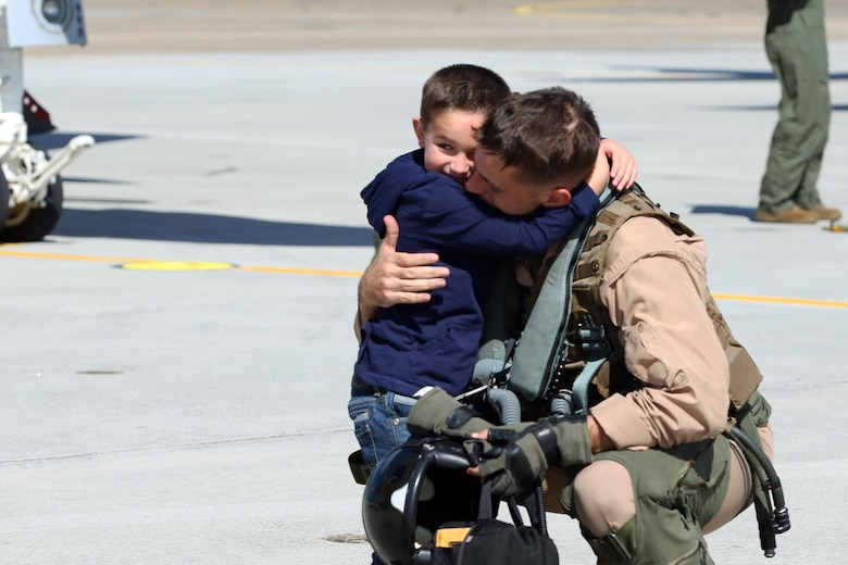 A Marine with Marine Tactical Electronic Warfare Squadron 4 embraces his son during a deployment homecoming aboard Marine Corps Air Station Cherry Point, N.C., Oct. 10, 2016. More than 20 air crew members with Marine Tactical Electronic Warfare Squadron 4 returned after a six-month deployment with the United States Central Command aboard Incirlik Air Base in Turkey. According to Lt. Col. Paul K. Johnson III, commanding officer for VMAQ-4, the Marines conducted electronic warfare and disrupted ISIS communications in Iraq and Syria in support of Operation Inherent Resolve. This deployment was the last that VMAQ-4 will participate in because the squadron is scheduled to be deactivated in the summer of 2017. (U.S. Marine Corps photo by Lance Cpl. Mackenzie Gibson/Released)