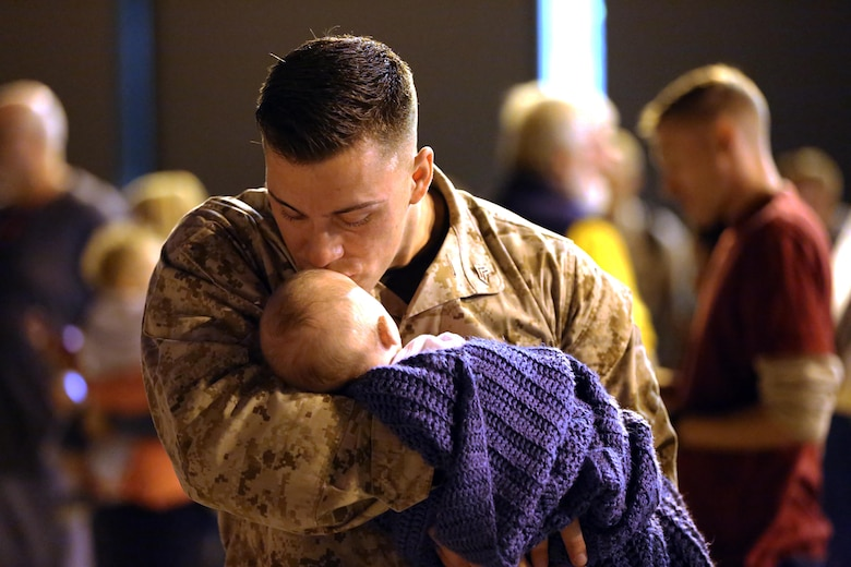 A Marine holds his son for the first time during a deployment homecoming aboard Marine Corps Air Station Cherry Point, N.C., Oct. 15, 2016. More than 120 Marines with Marine Tactical Electronic Warfare Squadron 4 returned after a six-month deployment with the United States Central Command aboard Incirlik Air Base in Turkey. According to Lt. Col. Paul K. Johnson III, commanding officer for VMAQ-4, the Marines conducted electronic warfare and disrupted ISIS communications in Iraq and Syria in support of Operation Inherent Resolve. This deployment was the last that VMAQ-4 will participate in because the squadron is scheduled to be deactivated in the summer of 2017. (U.S. Marine Corps photo by Lance Cpl. Mackenzie Gibson/Released)