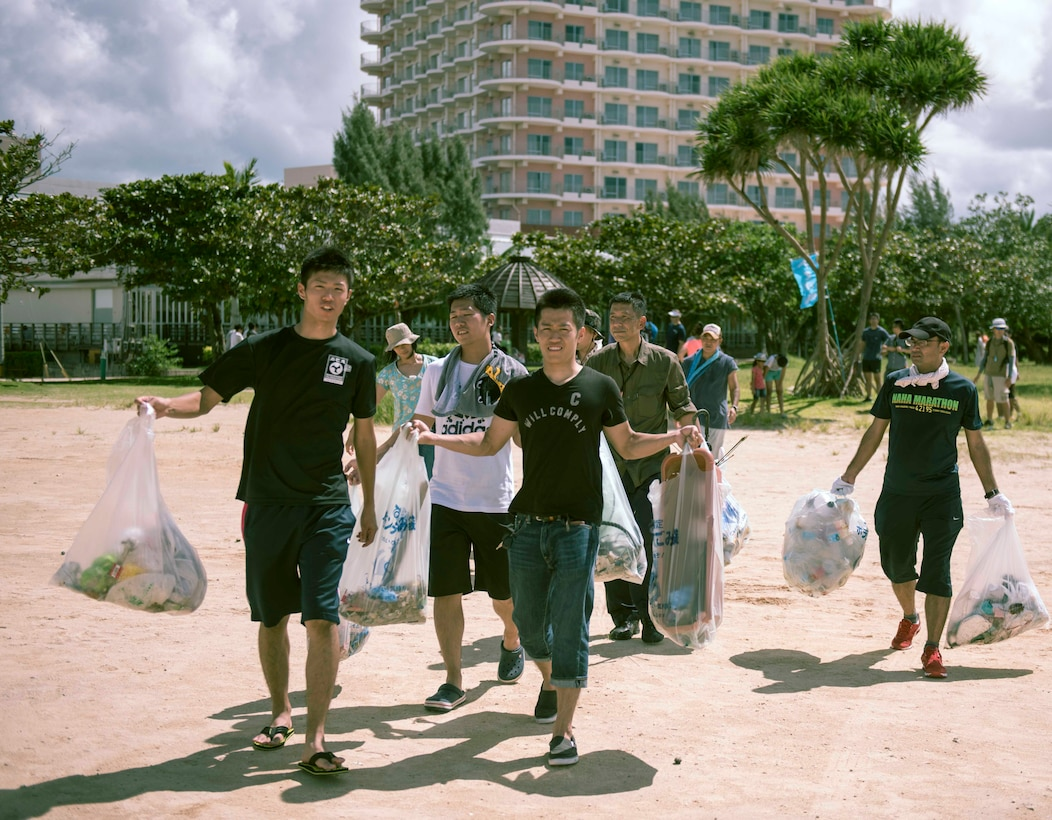 Japan Air Self-Defense Force members carry away trash collected during a beach cleanup Oct. 9, 2016, at Sunset Beach in Okinawa, Japan. Volunteers from Kadena and Naha Air Bases came together to build partnership and relations during the event. (U.S. Air Force photo by Senior Airman Omari Bernard)