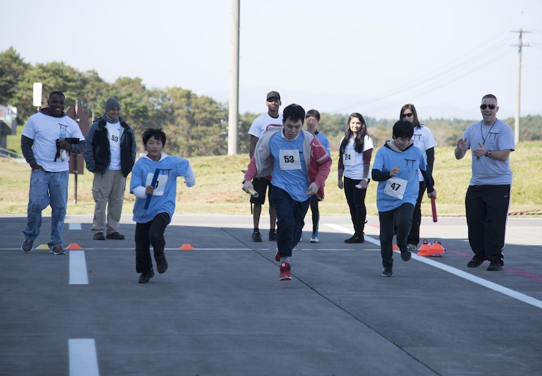 Keigo Imamiya, left, Izumi Yusuke, center, and Akemi Harata, right, Special Olympic athletes, participate in a 100-meter relay race during the 30th Annual Special Olympics at Misawa Air Base, Japan, Oct. 15, 2016. The event was held to get the local community involved and to continue to foster the relationship between the 35th Fighter Wing and Japanese nationals. (U.S. Air Force photo by Airman 1st Class Sadie Colbert)