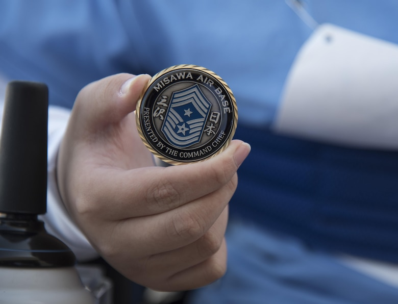 Yuichi Muraiyama, a Special Olympics athlete, shows his coin given by Chief Master Sgt. Charles Frizzell, the 35th Fighter Wing command chief, at Misawa Air Base, Japan, Oct. 15, 2016. Several distinguished visitors were present to show their support of the athletes. (U.S. Air Force photo by Airman 1st Class Sadie Colbert)