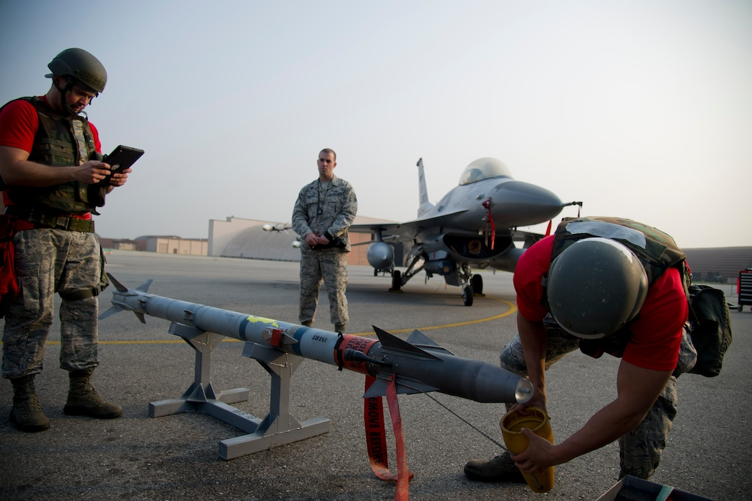 U.S. Air Force Staff Sgt. Jonathan Deacon, 36th Aircraft Maintenance Unit weapons load crew chief, and Senior Airman Zachary Ward, 36th AMU weapons load crew member, prepare an AIM-9 Sidewinder to be loaded onto an F-16 Fighting Falcon during the 51st Maintenance Group's Weapons Load Crew of the Quarter competition at Osan Air Base, Republic of Korea, Oct. 14, 2016. The best weapons load crew from the 25th and 36th AMUs battle it out every quarter to see which unit can most quickly reload munitions on their respective aircraft. (U.S. Air Force photo by Staff Sgt. Jonathan Steffen)